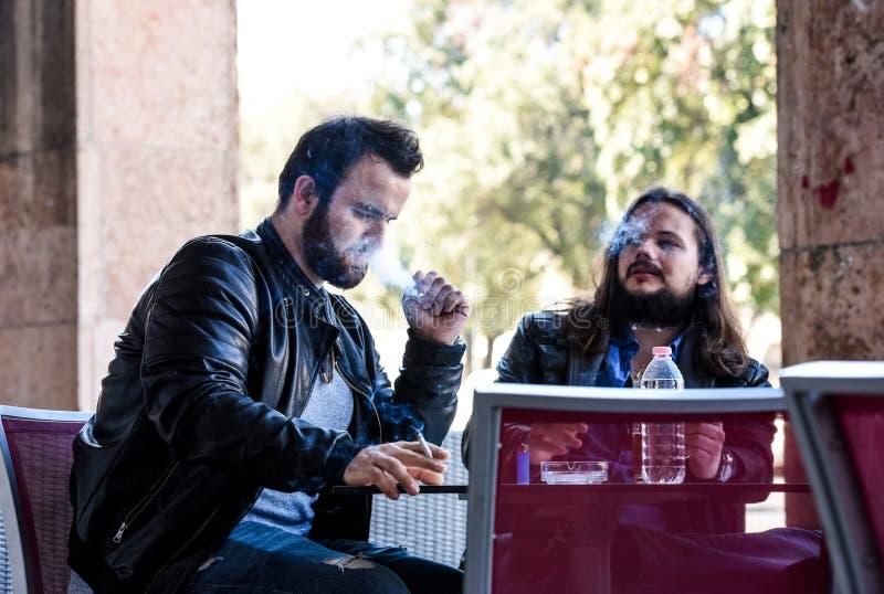 Ha en rök med ett öl Tända en cigarett royaltyfri foto