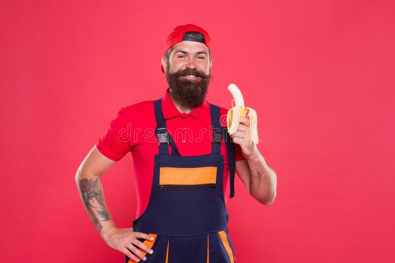 Ha en sund snack Bärgad man i uniform och med tak som äter banan Maskinellt kött av arbetare Färsk frukt arkivbilder