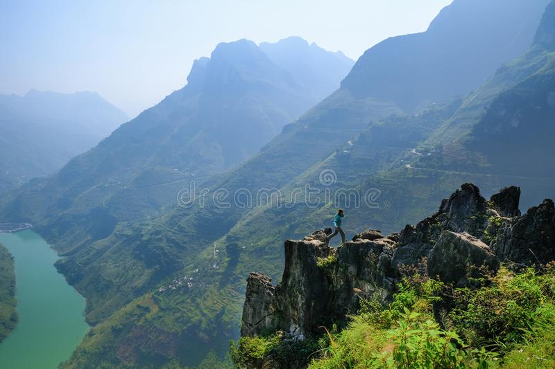 Ha Giang / Vietnam - 01/11/2017: Backpacker jumping on an outcrop overlooking a valley and karst mountains in the North Vietnamese royalty free stock photos