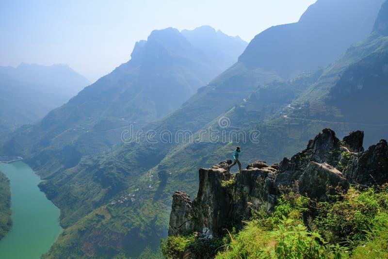 Ha Giang/Vietnam - 01/11/2017: El Backpacker que salta en un afloramiento que pasa por alto un valle y las montañas del karst en  fotos de archivo libres de regalías