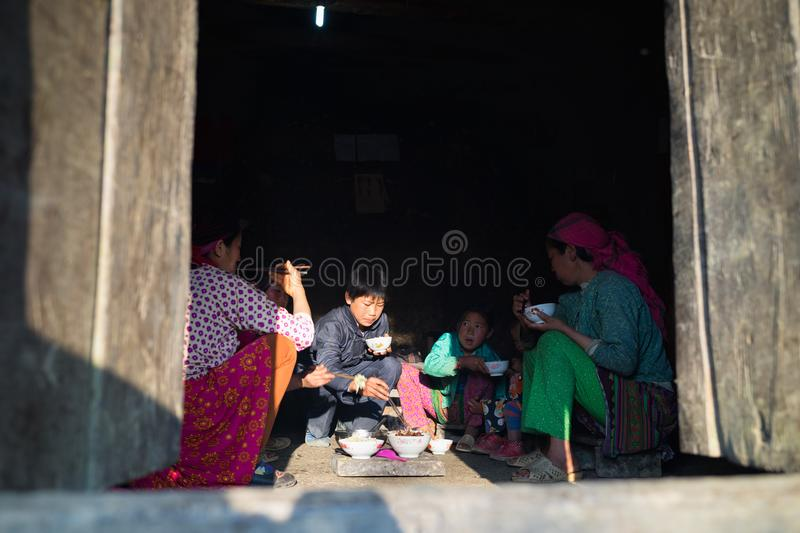 Ha Giang, Vietnam - Feb 13, 2016: H`mong ethnic minority family having lunch in their house in Yen Minh district, under sun beam. As source of light stock photo