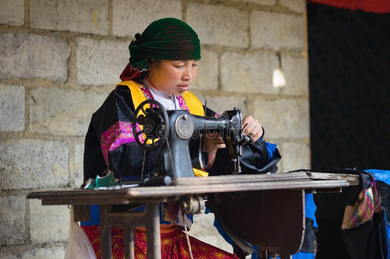 Ha Giang, Vietnam - Feb 14, 2016: H`mong woman making clothes by old sewing machine in front of her house in Van district.  royalty free stock photo