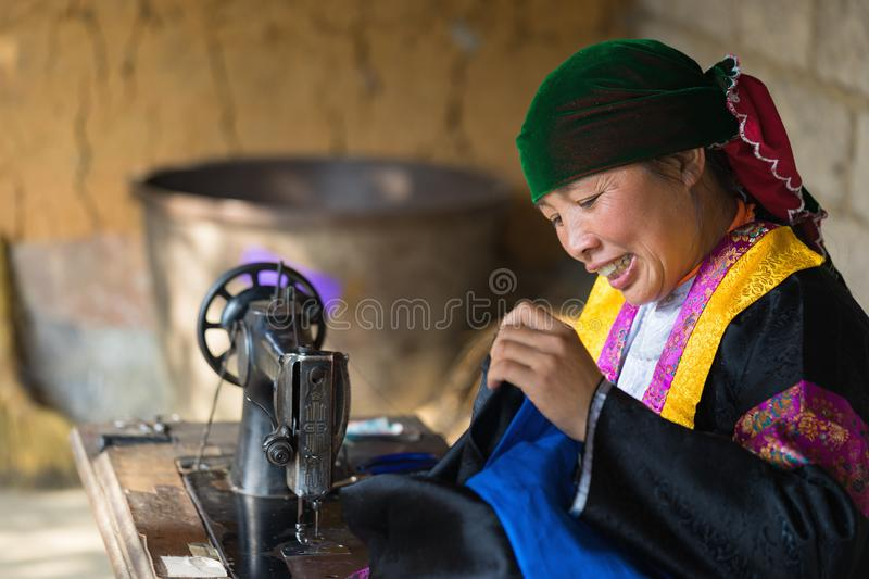 Ha Giang, Vietnam - Feb 14, 2016: H`mong woman making clothes by old sewing machine in front of her house in Van district.  royalty free stock photography