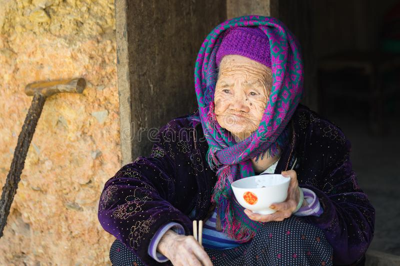 Ha Giang, Vietnam - Feb 14, 2016: Portrait of old Hmong woman having meal on door step in Van district.  royalty free stock photo