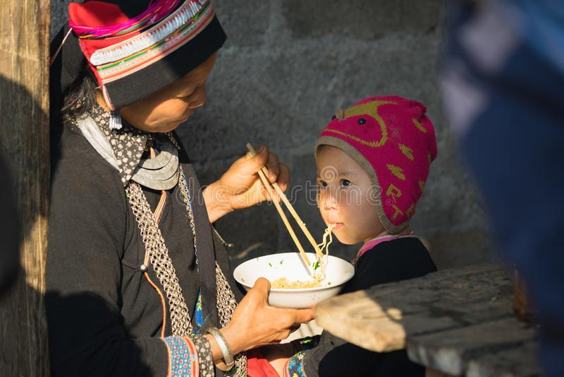 Ha Giang, Vietnam - 14 Februari, 2016: De Hmongmoeder voedt haar zoon met onmiddellijke noedel in Dong Van-Aziatische markt, royalty-vrije stock afbeeldingen