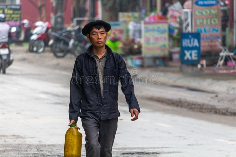 Yen Minh sunday meeting Vietnam. Ha Giang, Vietnam - March 17, 2018: Well dressed man from Hmong ethnic minority from the countryside walking to the sunday stock photography