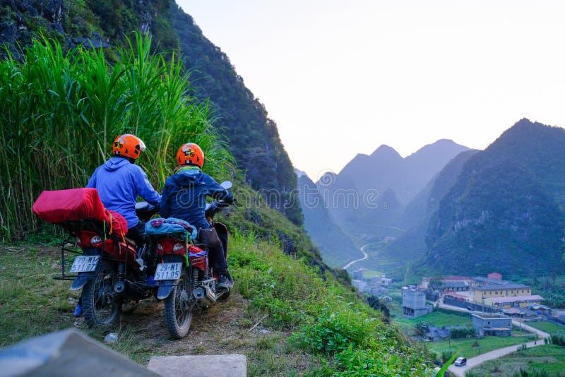 Ha Giang/Vietnam - 31/10/2017: Motorbikingsbackpackers bij het winden van wegen door valleien en karst berglandschap in het Noord stock foto