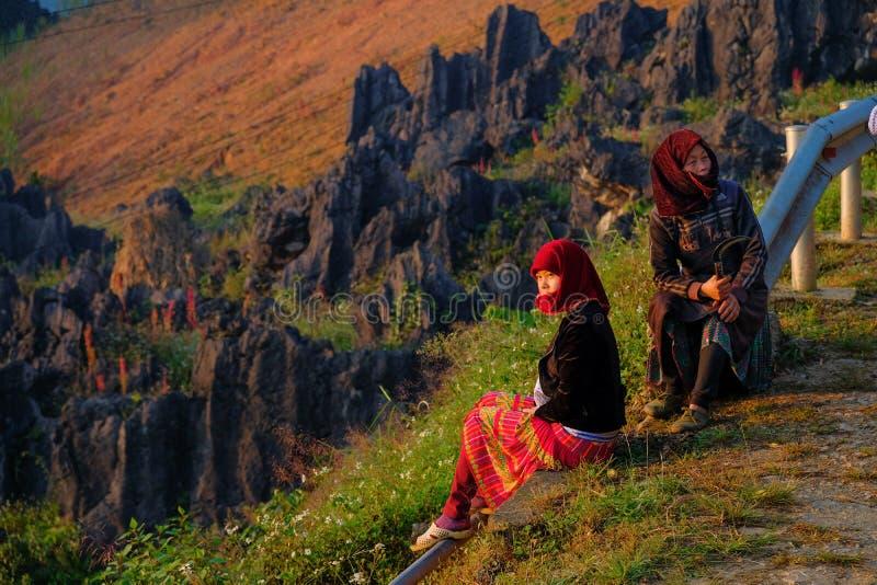 Ha Giang/Vietnam - 01/11/2017: Twee lokale Vietnamese vrouwen die in traditionele kleren de zonsopgang en het berglandschap binne stock foto's
