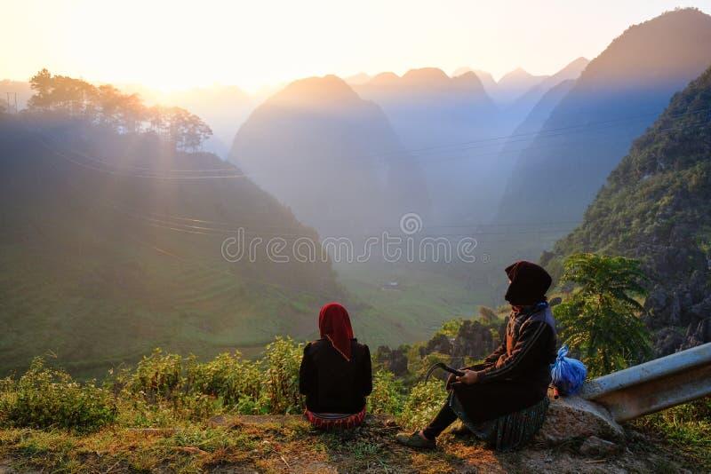 Ha Giang/Vietnam - 01/11/2017: Twee lokale Vietnamese vrouwen die in traditionele kleren de zonsopgang en het berglandschap binne royalty-vrije stock fotografie