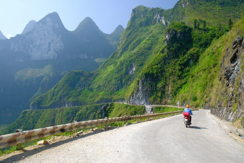 Ha Giang/Vietnam - 01/11/2017: Viaggiatori con zaino e sacco a pelo di Motorbiking sulle strade di bobina con le valli ed il paes fotografia stock libera da diritti