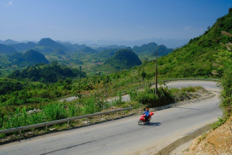 Ha Giang/Vietnam - 01/11/2017: Viaggiatori con zaino e sacco a pelo di Motorbiking sulle strade di bobina con le valli ed il paes fotografia stock