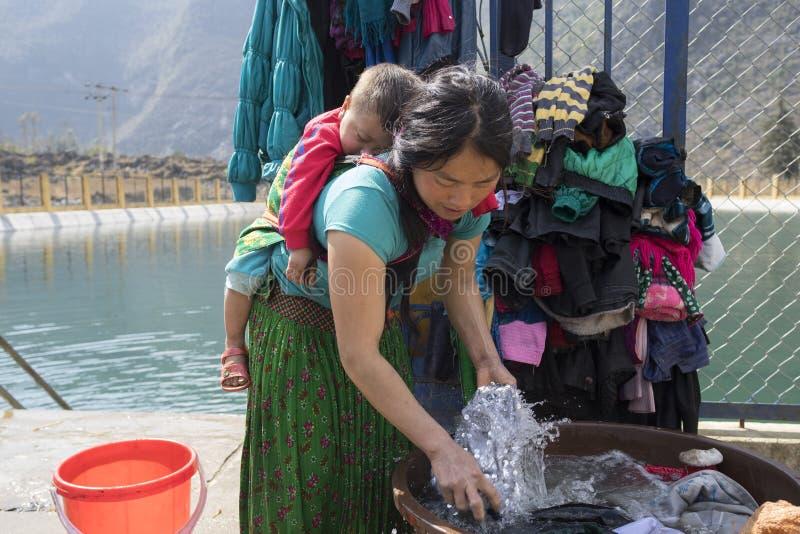 Ha Giang, Vietname - 7 de fevereiro de 2014: Roupa de lavagem da mãe muito nova não identificada de Hmong em um lago, com o filho fotos de stock royalty free