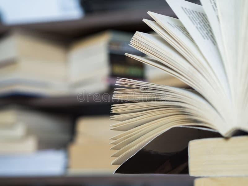 Ha impilato i libri ed offuscano il fondo sulla tavola di legno immagine stock