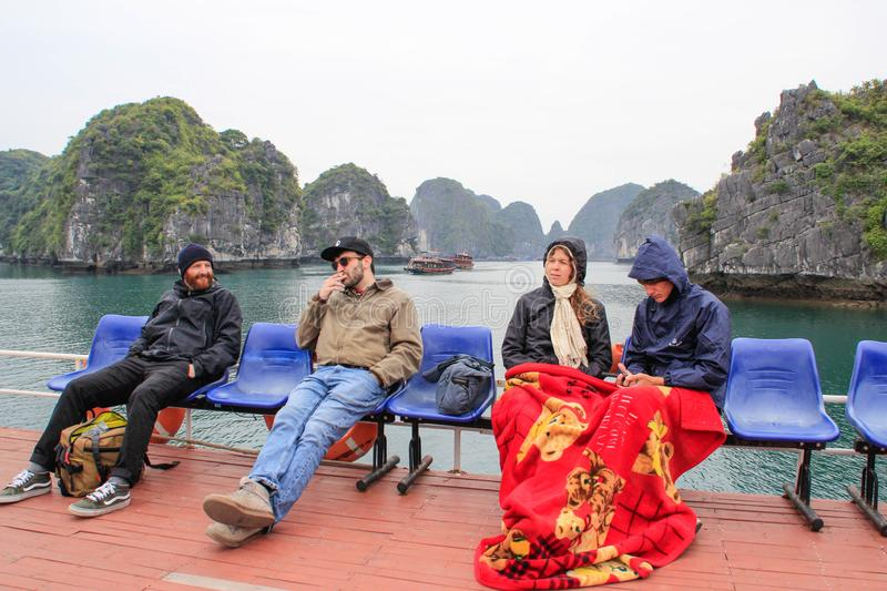 People on a cruise ship wrapped in blankets on a cold day in Ha Long Bay. Ha Long, Vietnam - February 17, 2016: people on a cruise ship wrapped in blankets on a royalty free stock image