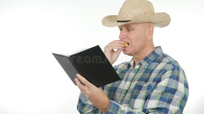 Ha morto di fame l'agricoltore Read From Agenda e mangiano un panino immagine stock