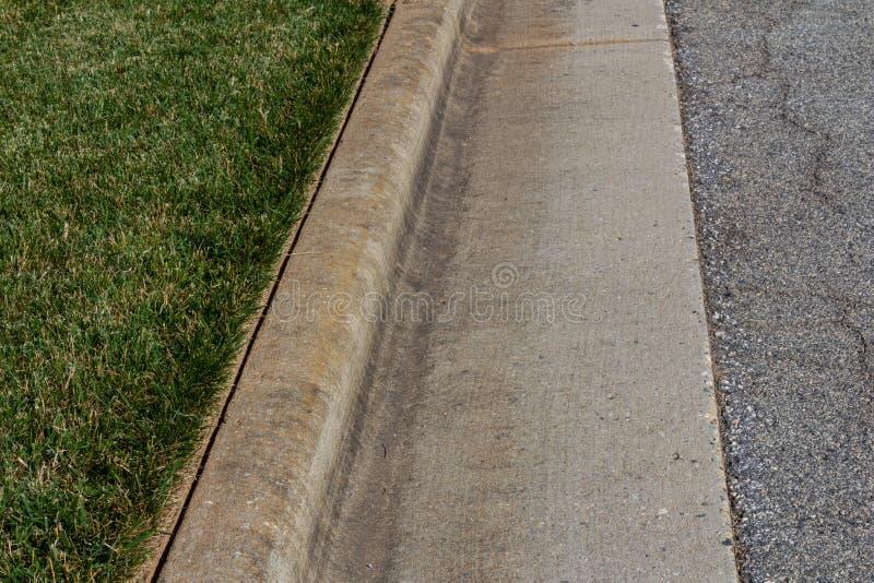 Ha orlato piacevolmente l'erba verde accanto ad un bordo concreto formato fotografia stock