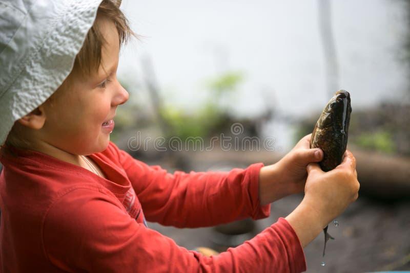 Ha pescato un piccolo pesce in palme del ` s dei bambini fotografie stock
