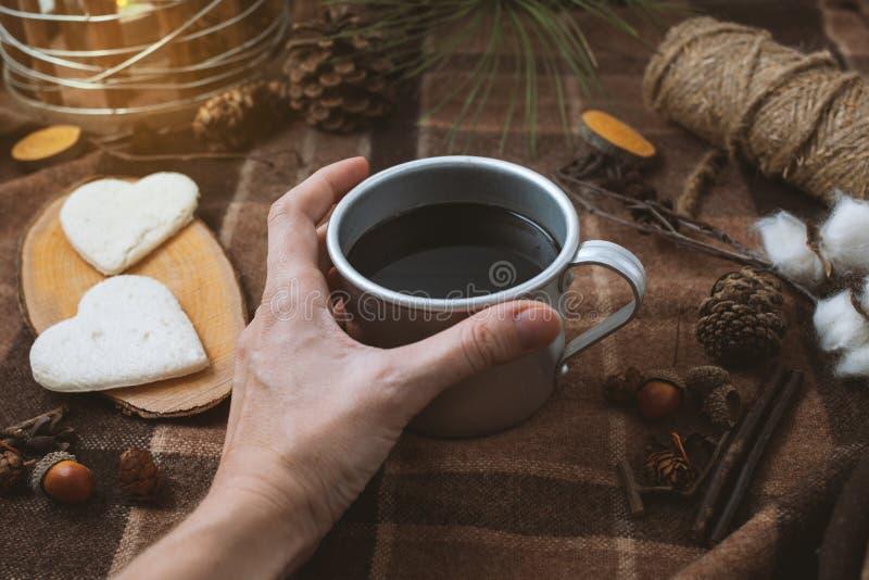 Ha picknick i natur, händer som rymmer en kopp av svart kaffe, pläd och hjärtor arkivfoton