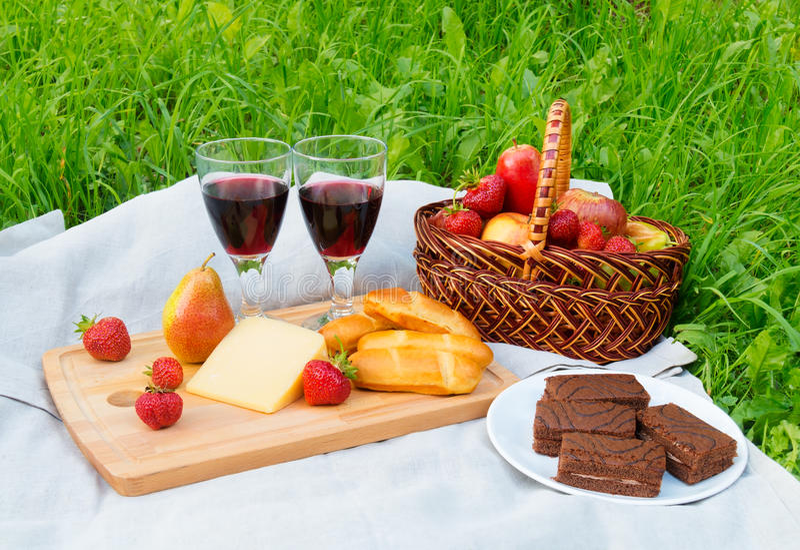 Ha picknick med rött vin, bröd, ost, chokladkakor och frukter royaltyfri foto