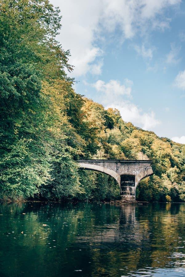 Ha rotto il ponte di pietra ad un fiume immagine stock