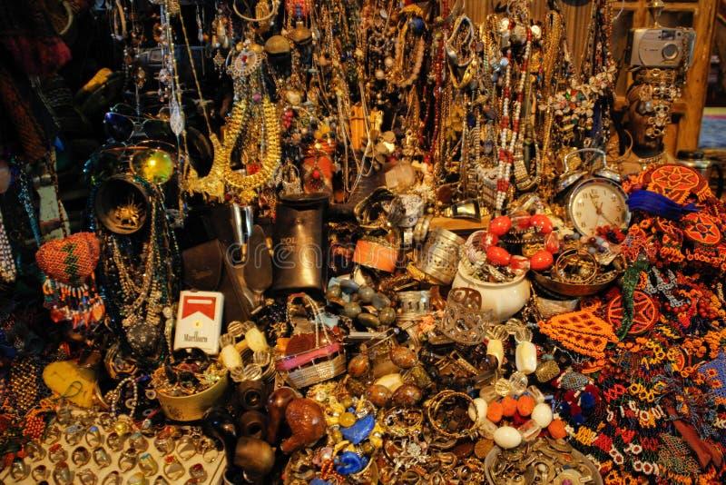 Ha sparso a caso i braccialetti, le perle, gli orecchini e gli anelli fatti dei metalli preziosi e delle pietre sul mercato di Co fotografie stock