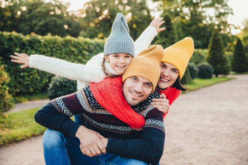 Ha trevlig tid tillsammans! Le den upphetsade kvinnan, bär mannen och deras lilla kvinnliga barn, varm stucken kläder, omfamnar s arkivbilder