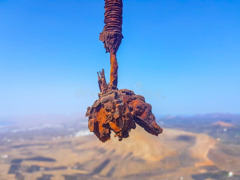 Haak van de met elkaar verbonden kabels van de draadlijn roestig in de voorgrond met hemel en overzeese bodem Beeld in Lanzarote, stock foto
