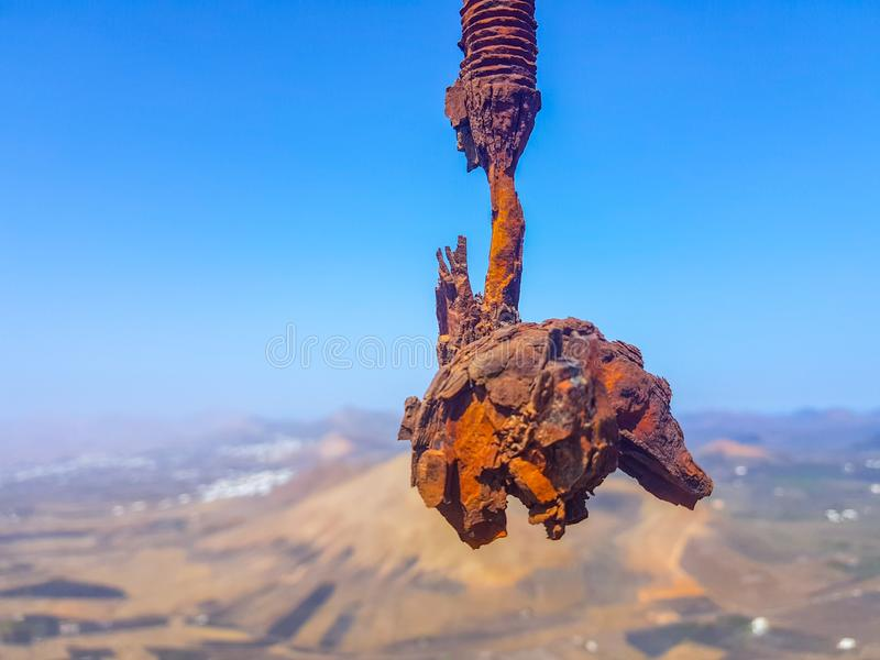 Haak van de met elkaar verbonden kabels van de draadlijn roestig in de voorgrond met hemel en overzeese bodem Beeld in Lanzarote, stock fotografie