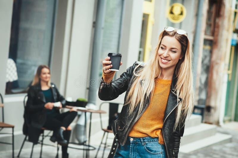 Haal koffie weg Het mooie jonge stedelijke vrouw dragen in zwarte modieuze koffie houden vormt en kleren die terwijl het lopen gl stock fotografie