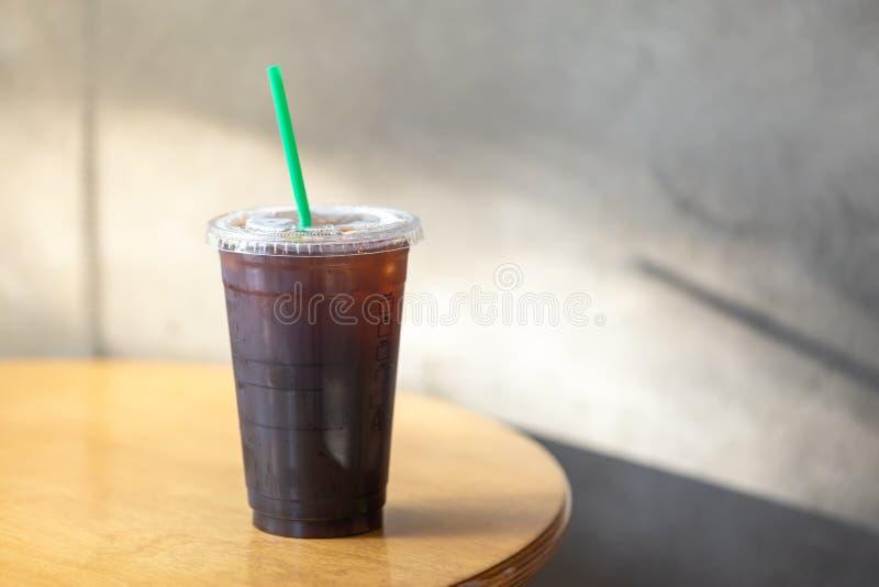 Haal plastic kop van bevroren zwarte koffie Americano op houten lijst met ochtendzonlicht weg stock foto's