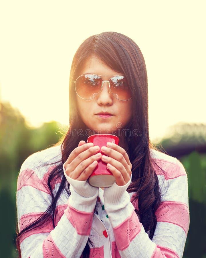 Haar-Abnutzungssonnenbrille der Hippie-Frauen übergibt lange das Halten des heißen Tasse Kaffees lizenzfreies stockfoto