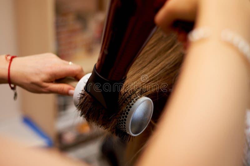 Haar, das eine Rundbürste anredet Trocknen und Legen auf einen runden Kamm stockfoto