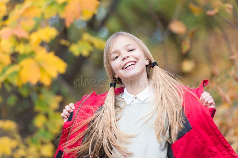 In haar eigen stijl De slijtagelaag van het jong geitjemeisje voor de aardachtergrond van het de herfstseizoen Kind vrolijk op da royalty-vrije stock afbeelding