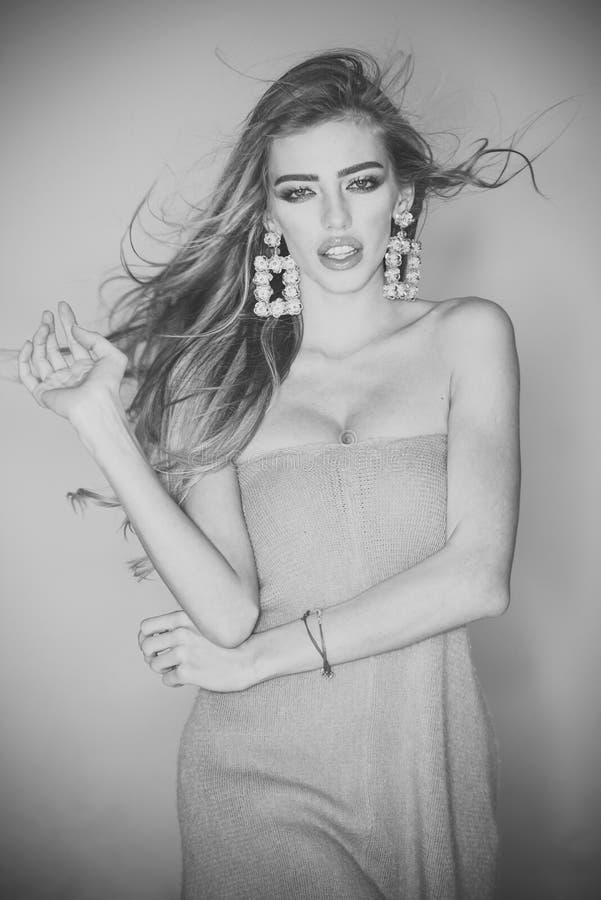 Haar-Schönheits-Konzept Dünne sexy Dame mit dem gelockten Haar Frau mit dem langen Haar und großem Ohrringschmuck schaut attrakti stockbild