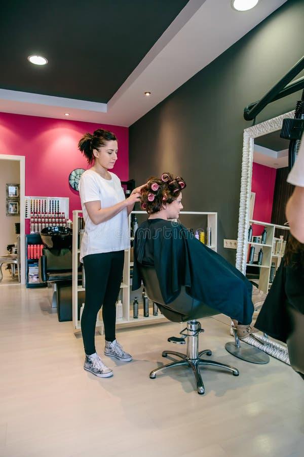 Haar van de kapper het krullende vrouw in een schoonheidssalon stock foto's