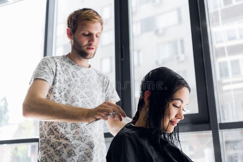 Haar van de kapper het scherpe cliënt ` s in salon met schaarclose-up Het gebruiken van een kam royalty-vrije stock fotografie