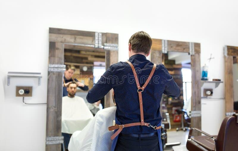 Haar van de kapper het scherpe mannelijke cliënt bij herenkapper royalty-vrije stock fotografie