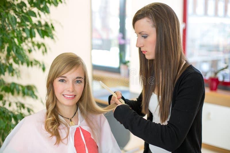 Haar van kapper het scherpe klanten in salon stock fotografie