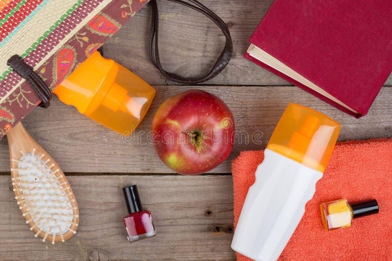 Haarbürste, orange Tuch, Sonnencreme, Lotion, Strandtasche, Nagellack, ein Buch auf einem braunen hölzernen Hintergrund stockbilder