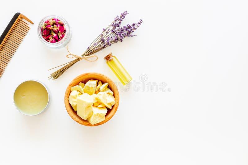 Haarbehandlung mit Naturprodukten Buxacee, Argan, Kokosnussöl nahe Bündel Lavendel und Haarbürste auf Weiß lizenzfreies stockfoto