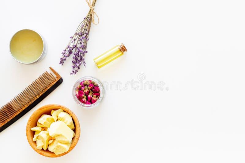 Haarbehandlung mit Naturprodukten Buxacee, Argan, Kokosnussöl nahe Bündel Lavendel und Haarbürste auf Weiß stockbild