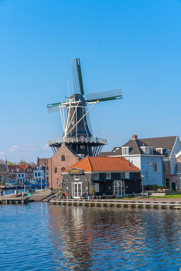 """Haarlem Nederländerna †""""April 14, 2019: Sikt av Harlem Cityscape med De Adriaan Windmill på den Spaarne floden på bakgrund på m royaltyfri foto"""