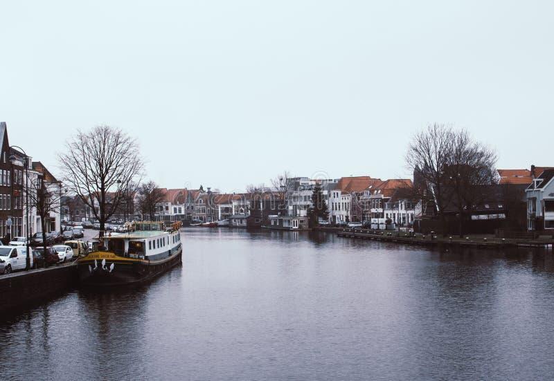 Haarlem Nederländerna - Februari 5, 2019: Lugna sikt av den Spaarne floden i Haarlem, Nederländerna Mörka skuggor gjuter på royaltyfri foto