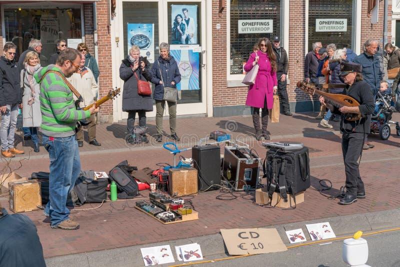 """Haarlem, Nederland †""""14 April, 2019: een straatmusicus met een gitaar en een zanger op een stadsstraat royalty-vrije stock afbeeldingen"""