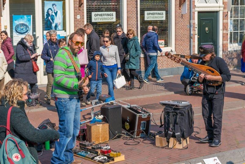 """Haarlem, Nederland †""""14 April, 2019: een straatmusicus met een gitaar en een zanger op een stadsstraat royalty-vrije stock fotografie"""