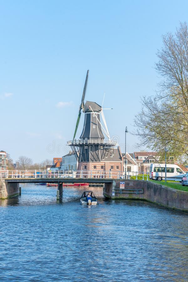 Haarlem, Netherlands – April 14, 2019: View of Harlem Cityscape With De Adriaan Windmill on Spaarne River On Background At Noon. In Haarlem, The stock photography