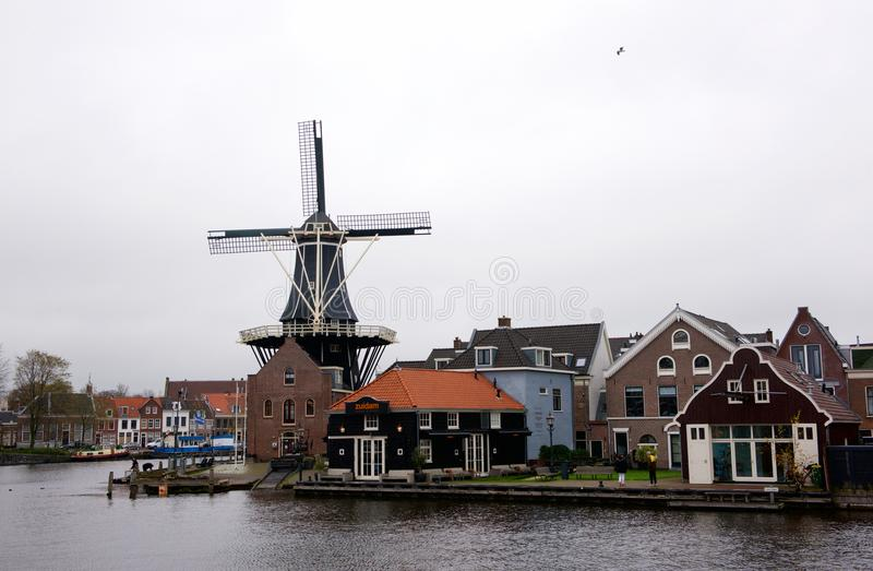 HAARLEM, THE NETHERLANDS - NOV 14: typical windmill and medieval architecture in Haarlem on 14 Nov, 2017. It`s known as De Adriaan royalty free stock image