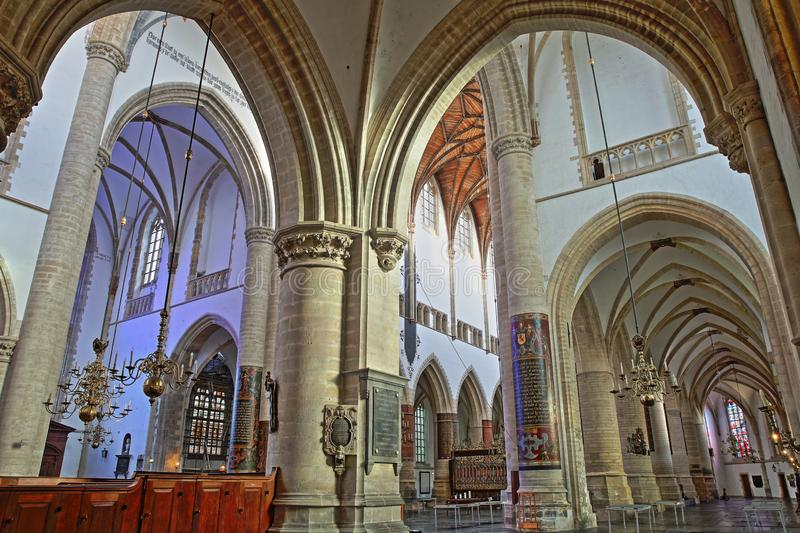 The interior of St Bavokerk Church, with the nave and the transept viewed through arches and columns stock image