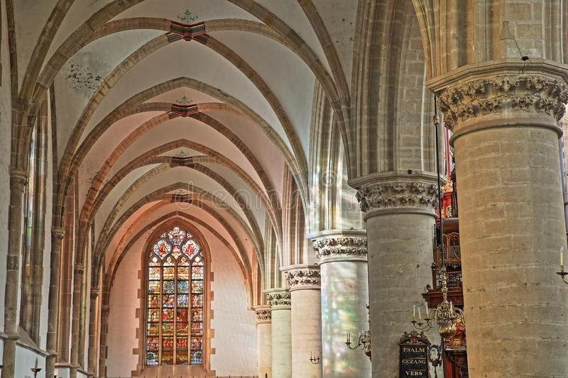 The interior of St Bavokerk Church, with stained glasses and alignement of columns and arches stock images