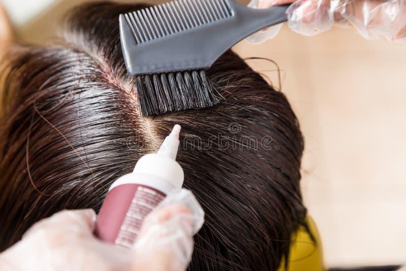Haaropmaker die de chemische kleurstof van de haarkleur op haarwortels toepassen royalty-vrije stock afbeelding